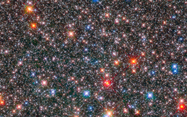 Picture of a crowded field of stars some red, some blue of varying brightness